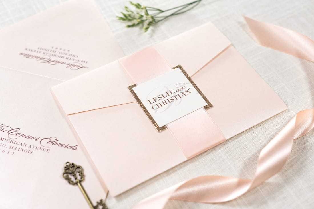 elegant and formal ivory, rose gold glitter, and blush metallic shimmer pocketfold wedding invitation suite with satin ribbon belly band and monogram square
