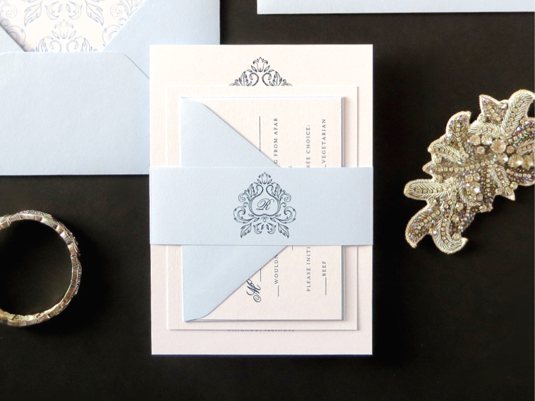 ELEGANT AND FORMAL ORNATE MONOGRAM CREST WEDDING INVITATION IN WHITE, PALE SERENITY BLUE AND ICE SILVER