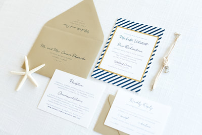 modern nautical wedding invitation layered with navy blue stripe pattern, gold foil, gold shimmer, and white